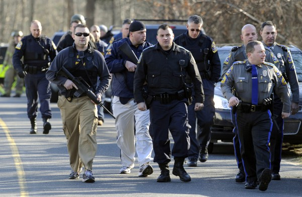 Law enforcement officials canvass the area following a shooting at the Sandy Hook Elementary School in Newtown, Conn., about 60 miles northeast of New York City, Friday, Dec. 14, 2012.