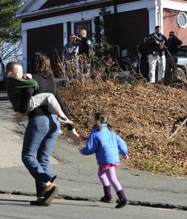 A mother runs with her children as police above canvass homes in the area following a shooting at the Sandy Hook Elementary School in Newtown, Conn., about 60 miles northeast of New York City, Friday, Dec. 14, 2012.