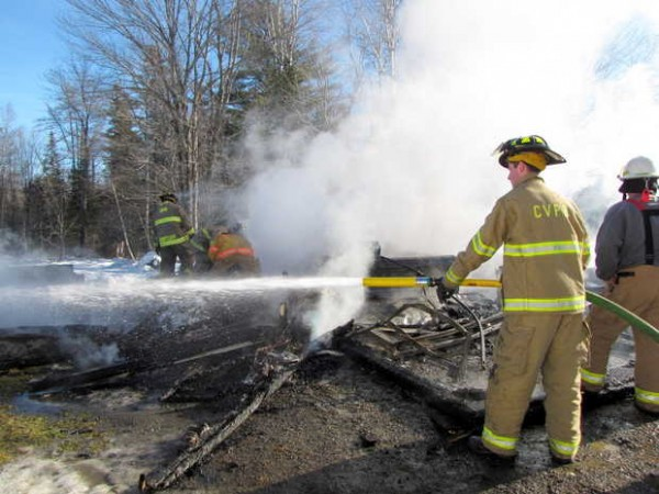 Firefighters sift through the rubble for fire spots Wednesday after a garage and its contents were destroyed at 791 Foster Hill Road in Freeman Township.