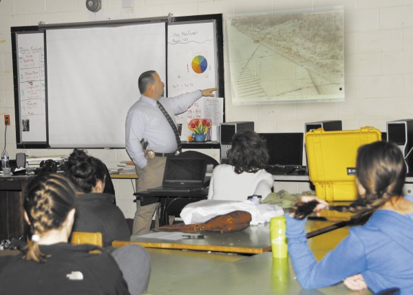 Detective Jay Munson, a forensic photographer for the Brewer Police Department, gives a presentation to Brewer High School photography students. Munson covered the importance and proper procedure of shooting a crime scene. Here, he points out tire tracks in the path of a vehicle that crashed.