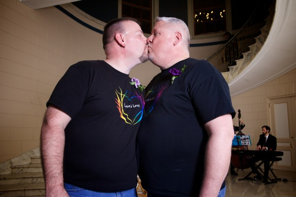 Steven Bridges (left) and Michael Snell smooch at Portland City Hall Saturday morning just after midnight, the first gay couple in Maine to tie the knot.