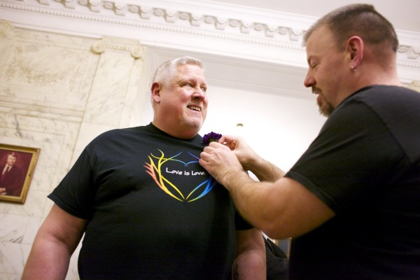 Michael Snell (left) receives a boutonniere by Steven Bridges before waiting in line to get married at Portland City Hall Friday evening.