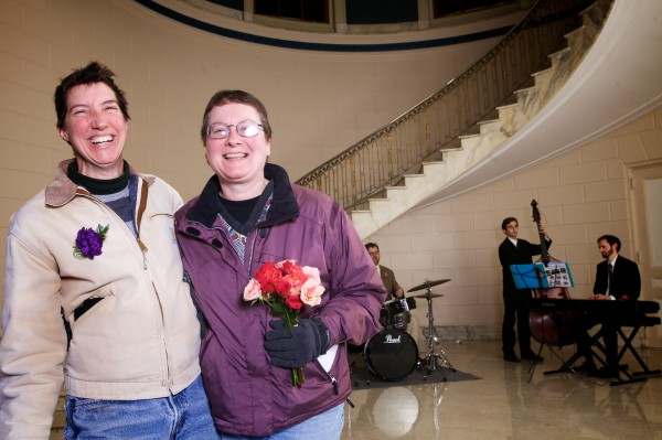 Newlyweds Wendy West (left) and Rebecca Leeman celebrate in the lobby of Portland City Hall Saturday morning, just after midnight.