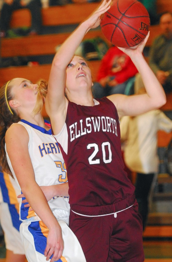 Ellsworth's Taylor White (20) takes a jump shot over Hermon's Shelby Caron (33) in third-period action at Hermon High School, Monday night, Dec. 17 2012. Hermon won 52-43