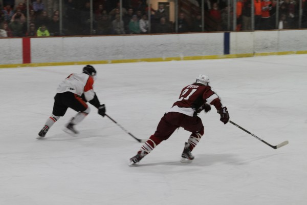 Gabe Valley #4 of Brewer and and Sam Huston #21 of Bangor race to the puck, at Saturday Nights Varsity Hockey Game at the Penobscot Ice Arena.