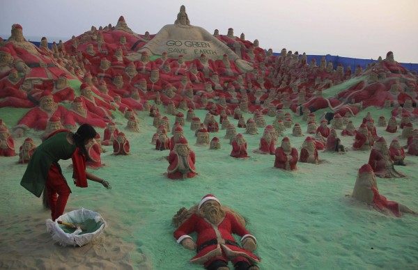 A student of the sand artist Sudarshan Pattnaik spreads colored powder in between sand sculptures of Santa Clauses on a beach in Puri, located in the eastern Indian state of Odisha, Dec. 25, 2012.