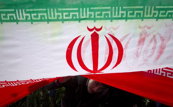 A demonstrator peeks from under an Iranian flag during a ceremony to mark the 33rd anniversary of the Islamic Revolution, in Tehran's Azadi square in this February 11, 2012 file photo. Picture taken February 11, 2012.