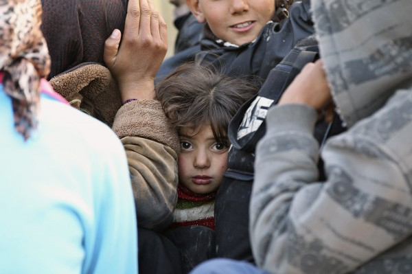 A girl looks on as she sits with other Syrian refugees fleeing violence on a Jordanian army vehicle, after crossing into Jordanian territory, near the town of Ramtha, on Wednesday, Dec. 26, 2012.