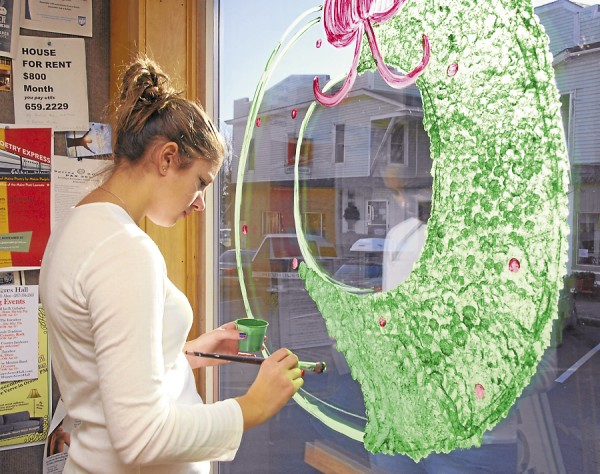 At Ampersand on Mill Street in Orono, Jillian Woodward of Orono paints a large window wreath on Thursday, Nov. 29 as part of a window-painting project partially funded by the Orono Village Association. Woodward is a student at Orono High School.