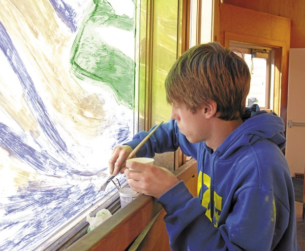 Joey Manning of Orono paints a wintry scene on a window at Ampersand on Mill Street in Orono on Thursday, Nov. 29. A student at Orono High School, Manning was participating in a downtown window-painting project partially funded by the Orono Village Association.