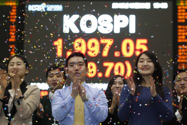 Employees of the Korea Exchange pose in front of the final stock price index during a photo opportunity for the media at the ceremonial closing event of the 2012 stock market at the Korea Exchange (KRX) in Seoul December 28, 2012. South Korean shares finished the year higher on Friday boosted by heavyweight Samsung Electronics in a thin trading session despite the unresolved U.S. fiscal negotiations and the slide of automakers. The Korea Composite Stock Price Index (KOSPI) rose 0.5 percent to close at 1,997.05 points, a one-week high.