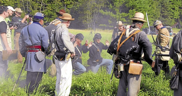 Maine Public Broadcasting Network Art Director and Producer Dan Lambert (far left) watches as two Union soldiers surrender to Confederate infantrymen at Good Will Hinckley School in Fairfield on Aug. 25, 2012. Lambert and a camera crew filmed the scene for inclusion in the MPBN documentary titled &quot16th Maine at Gettysburg.&quot Among the other MPBN staffers working that day was videographer Chad Diamond (third from the left).