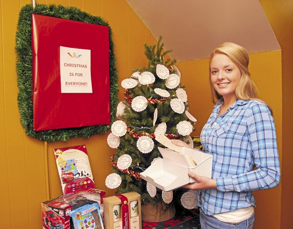 "Meredith Bean, a receptionist at Manna, reviews the cards of people who have signed up for Manna's 2012 ""Adopt A Family"" program. Behind Bean is a Giving Tree decorated with paper bulbs marked with specific clothing items that needy Mainers have requested. Generous Mainers are invited to stop by Manna at 629 Main St., Bangor to ""adopt"" a family and purchase presents for its members this Christmas season."