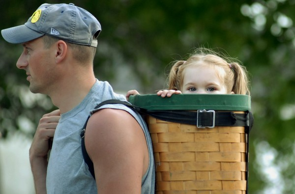 Maeve Pelletier, 2, of Orrington peeks out of her dad, Jay's, pack basket as he carries her around the American Folk Festival on Aug. 25, 2012.