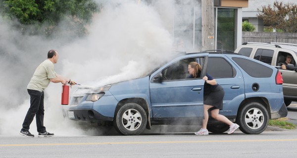Passers-by including Lincoln fireman Cory Stratton (left) and an unidentified woman try to extinguish a car fire on Union Street in Bangor just after 10 a.m. Thursday, Aug. 2, 2012.