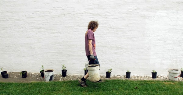 Asa Marsh-Sachs, employee at the Central Street Farmhouse downtown Bangor, carries buckets of soil while planting hops along the wall of the store.  The owners of Central Street Farmhouse are transforming the lot next to their business into an organic garden, a test kitchen for brewing beer, canning classes, and a multi-purpose outdoor space for events.