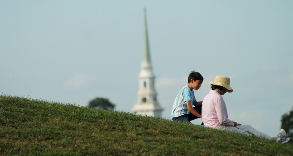 Sandra Tijerina and her son Santiago, 11, take a rest from the American Folk Festival on a hillside by the Dance Pavilion on Saturday afternoon, Aug. 25, 2012, in Bangor.