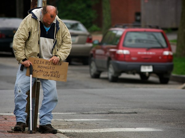 Don Deitz, 47, leans against a utility pole and holds his sign, waiting for a handout at the corner of State Street and Park Avenue in Portland on May 9, 2012. Deitz grew up just a few blocks away.