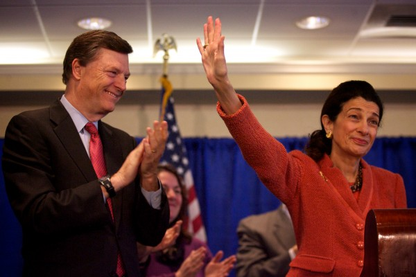 Sen. Olympia Snowe waves goodbye while husband, former Maine Gov. John McKernan, applauds on Friday, March 2, 2012, at a press conference in Portland.