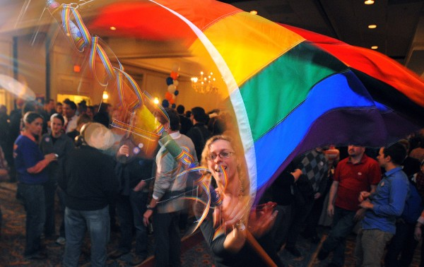 Angel Putney, of Portland spins a Gay Pride flag as she dences at the Mainers United for Marriage campaign party at the Holiday Inn in Portland. Hundreds of people gathered to watch the election returns on Tuesday night, Nov. 6, 2012.