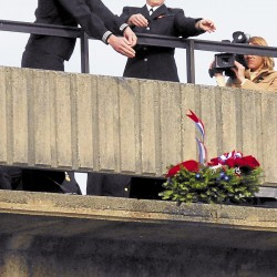 Two Navy Reservists, Petty Officer 2nd Class Stephen Lagueux of Portland and Senior Recruit Paige Laplante of Caribou, drop a wreath onto the Kenduskeag Stream during Pearl Harbor Day ceremonies held Friday, Dec. 7, 2012 on the Willard Carleton Orr Bridge spanning the stream in downtown Bangor.