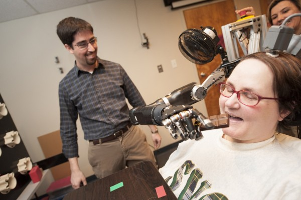 An undated photo shows a 52 year-old woman, paralysed from the neck down, demonstrating the use of a new mind-controlled prosthetic arm with intuitive control to help her eat a chocolate bar at the University of Pittsburgh Medical Centre in Pittsburgh. Researchers in the United States have developed a robotic arm controlled directly by thought with a level of agility closer than ever to a normal human limb.