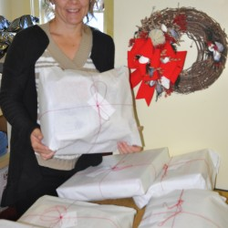 Susan Arthur, the Christmas Program Coordinator at the Maine Sea Coast Mission, shows off some of the wrapped packages that will be distributed to needy families as part of the organization's Christmas Program.