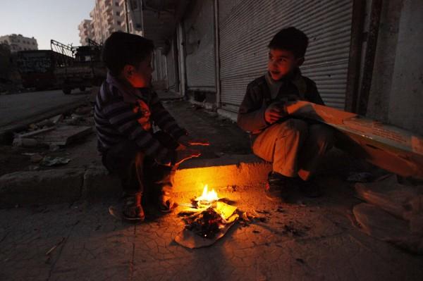 Two boys sit near a fire in the Bustan al-Qaser area in Aleppo, Syria, on Wednesday, Dec. 26, 2012.