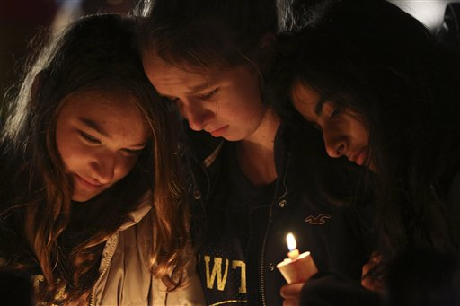 Kate Suba, left, Jaden Albrecht, center, and Simran Chand pay their respects at one of the makeshift memorials in honor of the victims of the Sandy Hook Elementary School shooting, Sunday, Dec. 16, 2012, in Newtown, Conn. A gunman opened fire at the school on Friday, killing 26 people, including 20 children before killing himself on Friday.