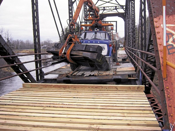 Volunteers from central Aroostook County snowmobile clubs and ATV clubs use heavy equipment to remove the weather-worn deck of a former railroad trestle spanning a stream in Stockholm. Timbers for a new deck are being laid in the foreground.