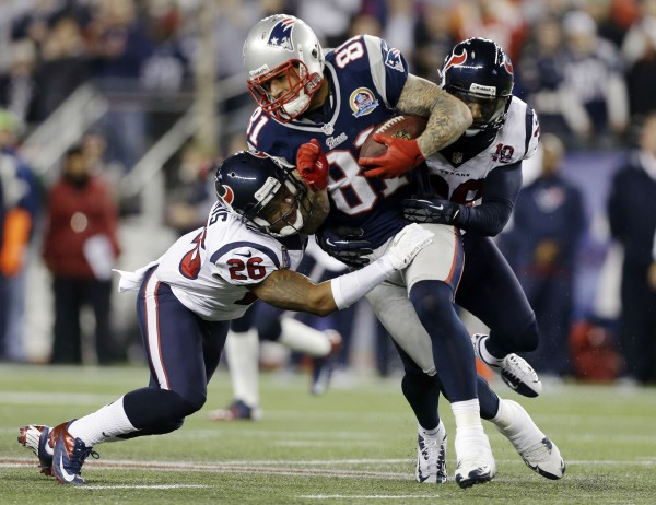New England Patriots tight end Aaron Hernandez (81) gains yards after a catch against Houston Texans defensive back Brandon Harris (26) and free safety Danieal Manning (38) during the second quarter of an NFL game in Foxborough, Mass., Monday, Dec. 10, 2012.