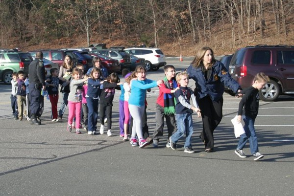 State police personnel lead children from the Sandy Hook Elementary School in this handout picture from the Newtown Bee, in Newtown, Connecticut, December 14, 2012. All public schools in Newtown, Connecticut, were placed in lockdown on Friday following a shooting at Sandy Hook Elementary School.