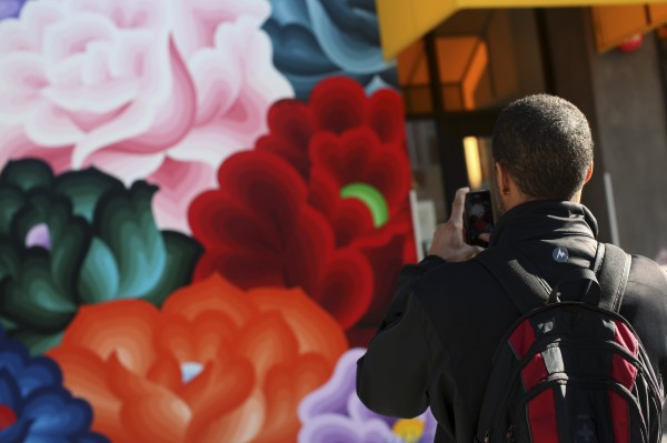 Carl Fisher uses a smartphone to snap a picture of a mural in the Mission District in San Francisco, Calif. on Tuesday, Dec. 18, 2012. Instagram, the popular photo-sharing service owned by Facebook Inc., said Tuesday it has &quotno plans&quot to incorporate user photos into ads in response to a growing public outcry over a new privacy policies unveiled this week.