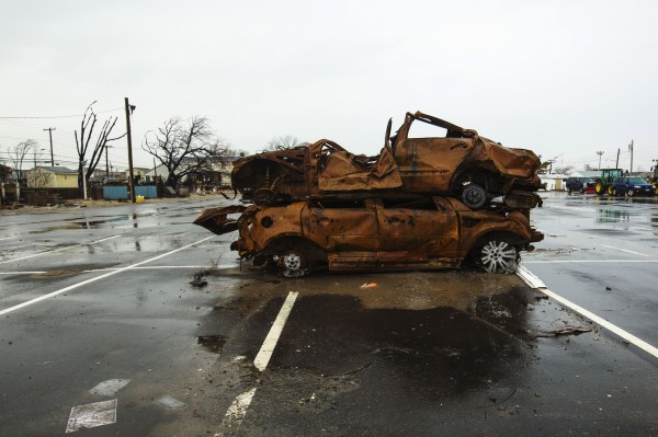 The remnants of two cars burned in a fire during Superstorm Sandy stand rusting in a parking lot in the Queens borough region of Breezy Point, New York, Dec. 29, 2012.