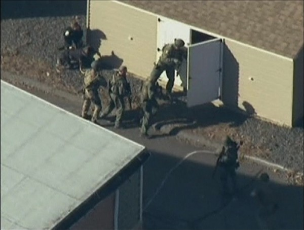 Police search a building after a shooting at Sandy Hook Elementary School in Newtown, Connecticut, December 14, 2012.
