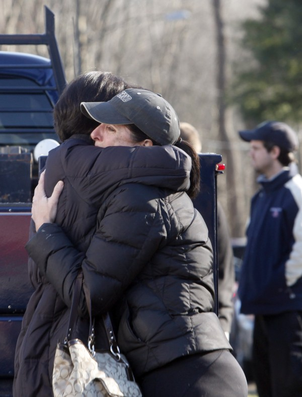 Relatives embrace each other outside Sandy Hook Elementary School following a shooting in Newtown, Connecticut, December 14, 2012.