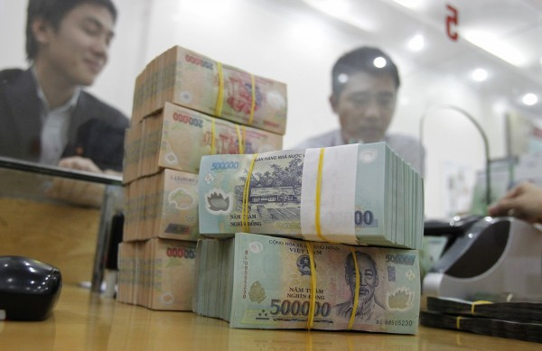 Men sit behind Vietnamese dong notes at a bank in Hai Phong city, east of Hanoi December 28, 2012. The State Bank of Vietnam plans to raise outstanding loans in the banking system by 12 percent in 2013, versus a rise of 7 percent this year, a state-run newspaper said on Friday.