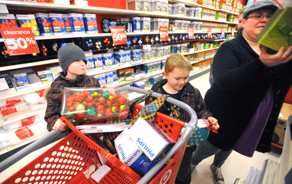 Andrea Harris of Jackson (right) shops for holiday decorations with her sons, Malachi Harris, 9, (left) Abishai Harris, 8, (center) and Eli Crandall, 14, (obscured), at Target in Bangor on Wednesday afternoon. &quotI always shop after these things go on sale to have decorations for next year,&quot she said. Also, her boys get some money for Christmas that they can spend after the holiday, and they mostly bought video game accessories this year. Erica Ireland, the leader on duty at the store, said that they have been very busy on Wednesday. &quotNot a lot of returned items, but people are out shopping using gift cards,&quot she said.