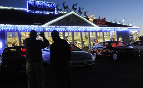 Darling's Honda employees watch and record the car dealership's Christmas light and sound show on Thursday, Dec. 6, 2012 in Bangor.