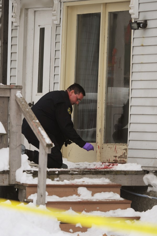 Bangor Police Detective Larry Morrill collects blood evidence from the deck and door of 80 Elm Street in Bangor on Saturday. A man has died after a reported stabbing at the residence.