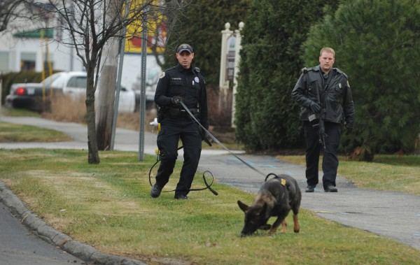 Bangor police officers Jason Linkletter (left) and Jason Stuart track a suspect in a pharmacy robbery along Husson Avenue in Bangor on Tuesday, Dec. 4, 2012.