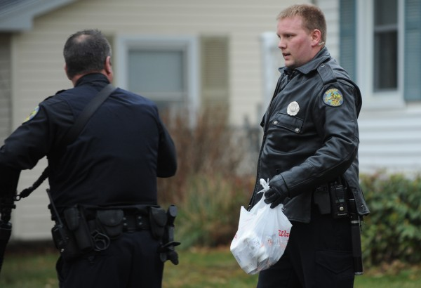 Bangor police officer Jason Stuart carries a Walgreens bag with pill bottles in it as evidence after police arrest a suspect behind 175 Falvey St. in Bangor on Tuesday, Dec. 4, 2012. The Walgreens on Broadway was the target of a pharmacy robbery earlier.