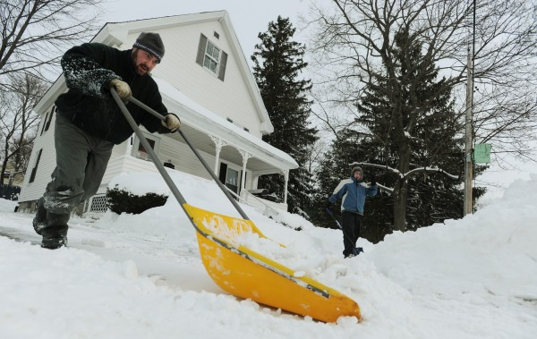 Matt LeClair (left) and his roommate John Kotredes (right) shovel and scoop the snow from Saturday's storm from their driveway and sidewalk along Savage Street in Bangor on Sunday.