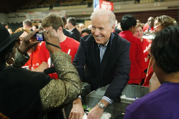 A volunteer stops to photograph Vice President Joe Biden as he helps assemble care kits for military service members and veterans at a Unite America in Service event at the National Guard Armory in Washington on Saturday.