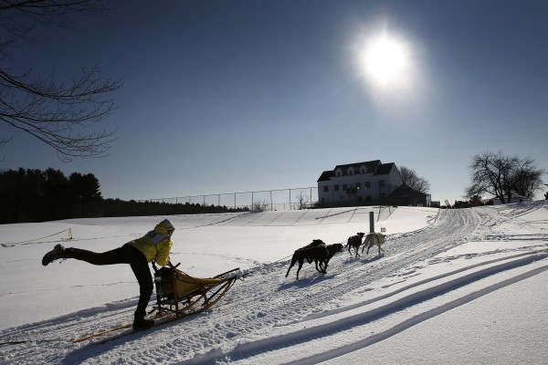 Sarah Vanderwood of Oxford kicks to assist her four-dog team as they head for the finish line in a race held by the New England Sled Dog Club at Sunset Ridge Golf Course in Westbrook on Sunday, Jan. 6, 2013.
