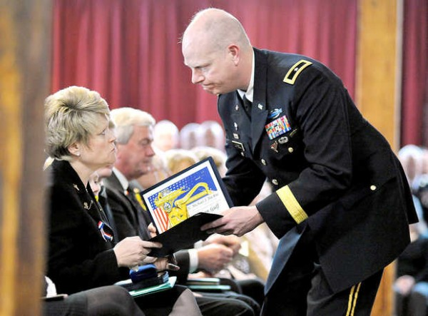 Kristie Backus is presented with the State of Maine Bronze Star for service during the funeral for LTC. Michael Backus in Farmington on Sunday.
