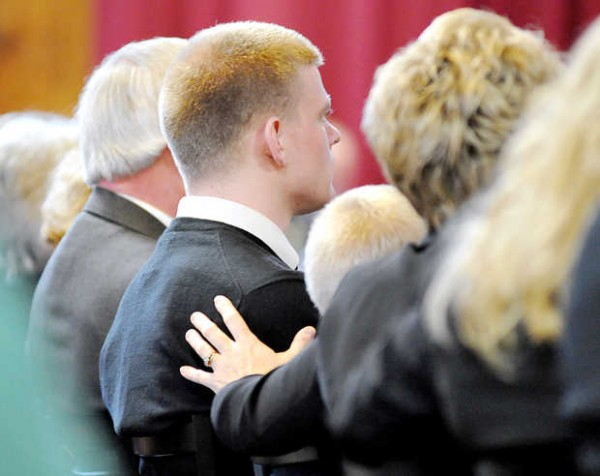 Kristie Backus offers a comforting touch to one of her three sons during the funeral for Lt. Col. Michael Backus on Sunday.
