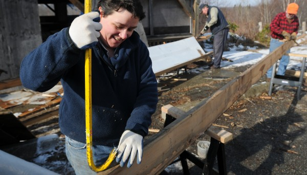 Jill Smith pulls nails from a piece of lumber that was taken from the former Country View Drive-In in Sedgwick.