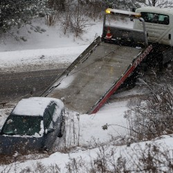 A flatbed driver prepares to haul a car out of the ditch on Washington Avenue in Portland Wednesday, Jan. 16, 2013 during snowy weather. In response top the snow, the city called a parking ban from 10 p.m. to 6 a.m.