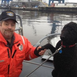 Harland Stanley shakes hands with Hoku after he and fellow Bath Iron Works security officer Sgt. Paul White rescued the dog Saturday morning, Jan. 12, 2013.
